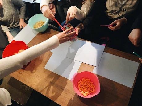 Bild tagen ovanifrån på ett bord med papper och händer som tar pennor ut en burk