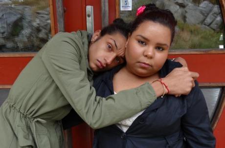 Foto: Två personer som  kramar om varandra och tittar in i kameran.