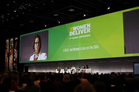 Bild på en scen på Women Deliver konferensen. En stor grön skärm syns bakom panelen.