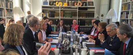 Bild på ett mötesrum där deltagare sitter runt ett bord och pratar med varandra
