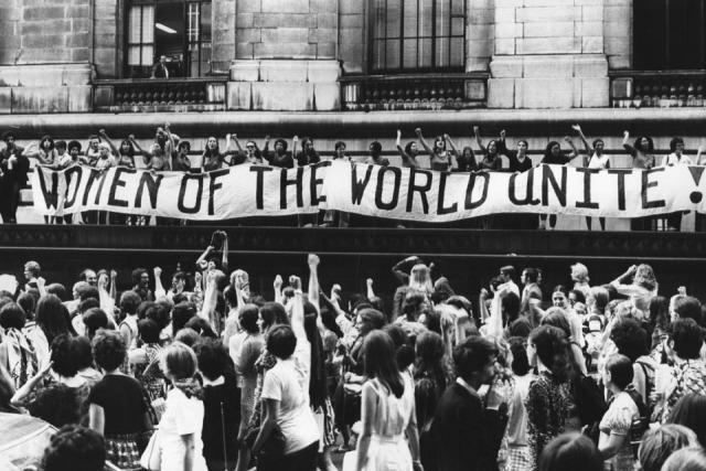 """Svartvit bild på människor under demonstration och en baner med texten """"women of the world unite!"""""""
