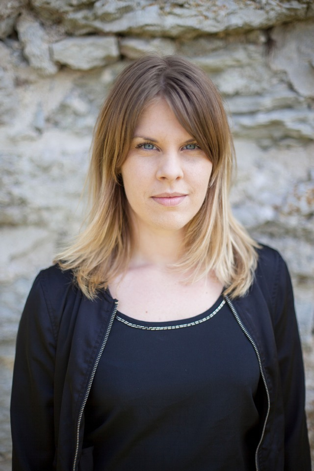 Foto: Emma står med svart jacka och tröja mot en grå stenvägg