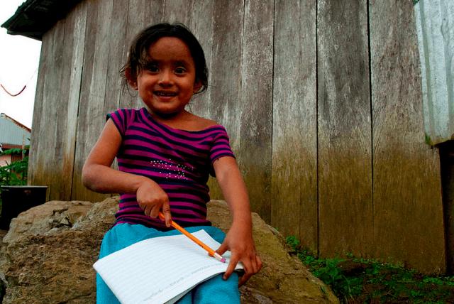 Foto: en liten flicka sitter på en sten, med ett block och en penna i handen.