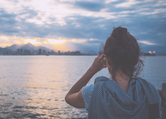 en tjej står och ser ut över vatten.