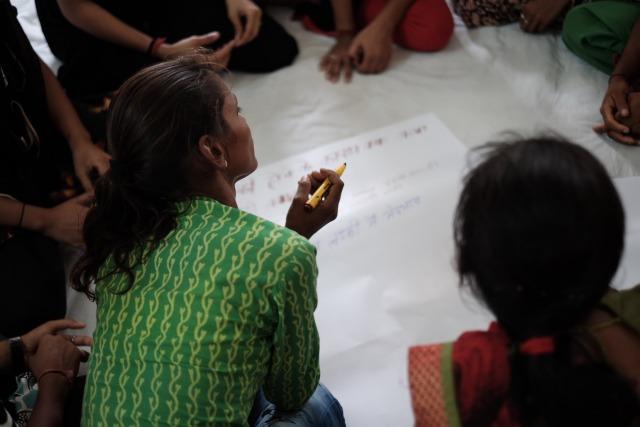 En flicka sitter i mitten av en grupp med en penna i handen. Framför henne ligger ett papper.