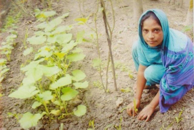 Foto: En flicka sitter hukad och planterar en växt i marken