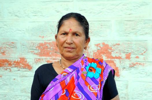 Foto: Shanti står framför en grön vägg och tittar in i kameran.