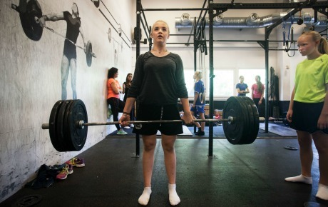 Tjejer som styrketränar. Hon ser fokuserad ut.